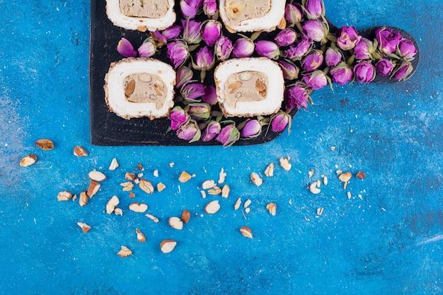Houten bord met zoete lekkernijen en gedroogde rozen op blauwe tafel.