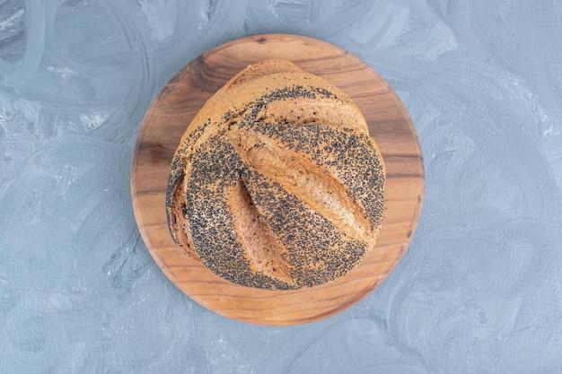 Houten bord onder een brood van zwarte sesam bedekt op marmeren tafel.