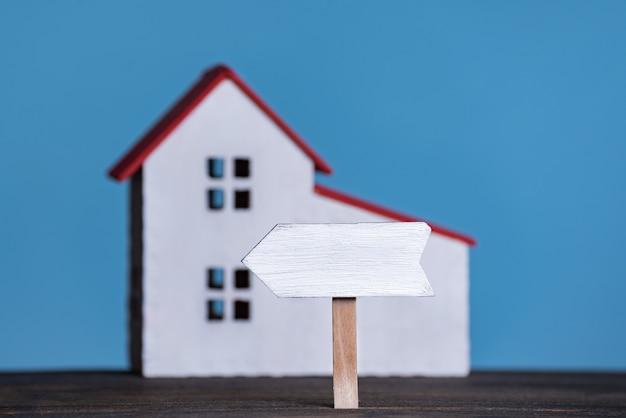 Houten bord op huis achtergrond. eigen accommodatieconcept. blauwe achtergrond, vooraanzicht