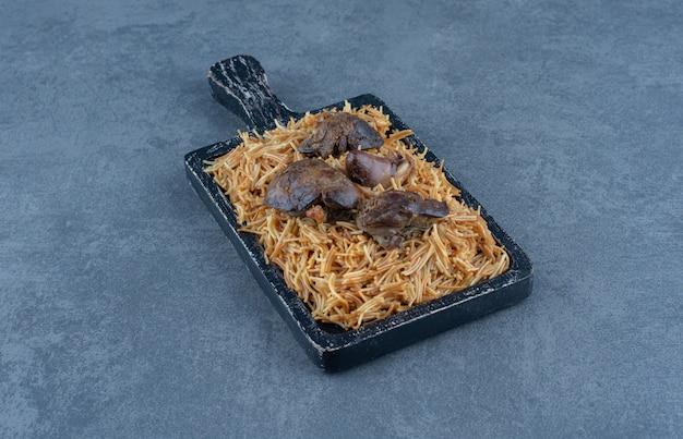 Houten bord pasta met droog vlees op stenen tafel.