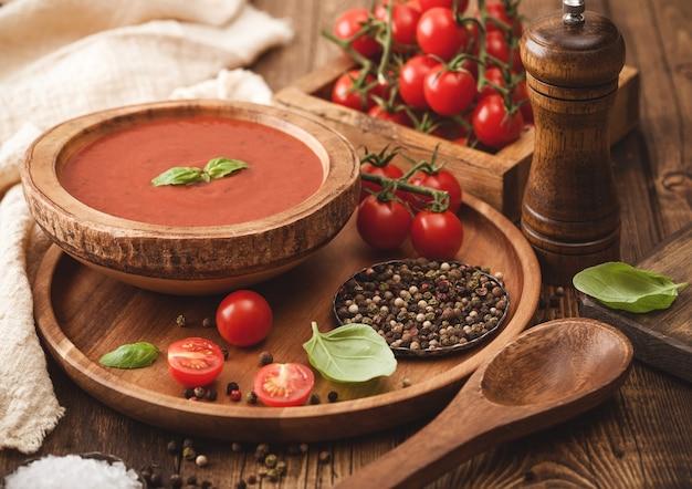 Houten bord romige tomatensoep 0n rond dienblad, peper en keukendoek op houten bord met doos rauwe tomaten.