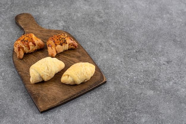 Houten bord van gemengde verse koekjes op stenen tafel.
