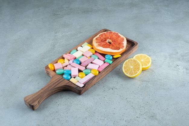 Houten bord van kleurrijke kauwgom en grapefruit op steen.
