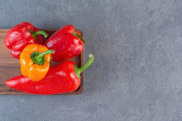 Houten bord van kleurrijke verse paprika op stenen oppervlak