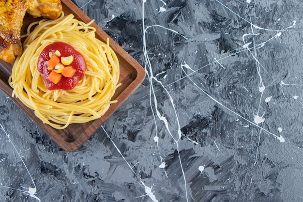 Houten bord van noedels met gebakken kippenvleugels op marmeren oppervlak.