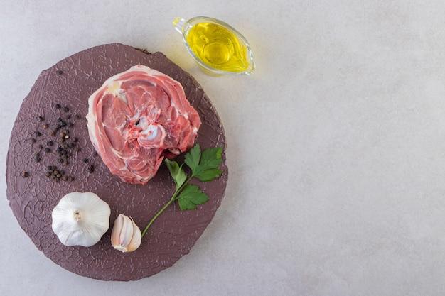 Houten bord van rauw vlees met knoflook en olie op tafel.