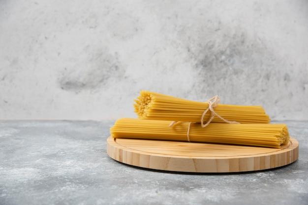 Houten bord van rauwe droge spaghetti op marmeren oppervlak.