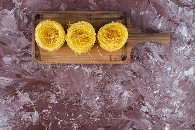 Houten bord van rauwe pasta nesten op marmeren oppervlak