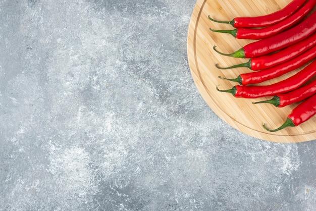 Houten bord van rode chilipepers op marmeren oppervlak.