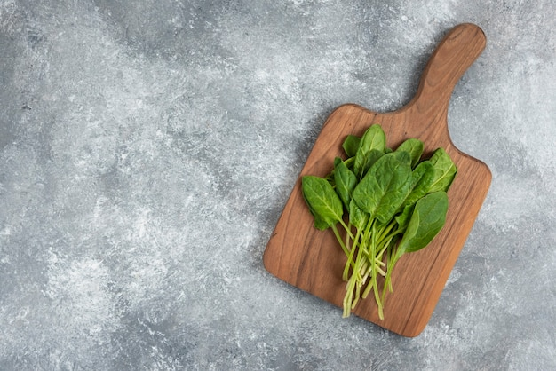 Houten bord van verse gezonde groene bladeren op marmer.
