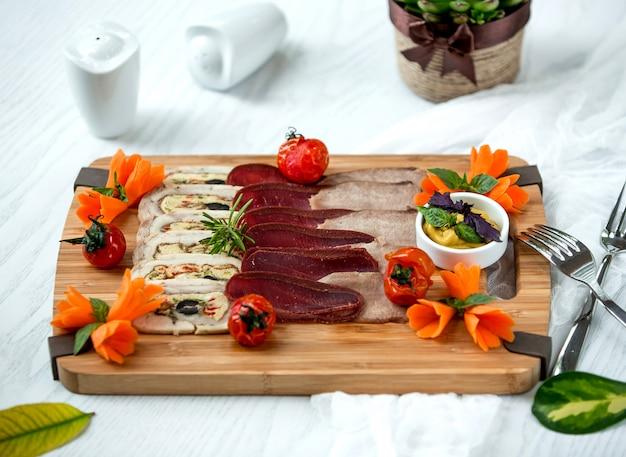 Houten bord van vlees bijgerechten gegarneerd met saus en groenten