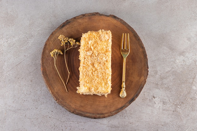 Houten bord van zelfgemaakte honingkoek op stenen oppervlak