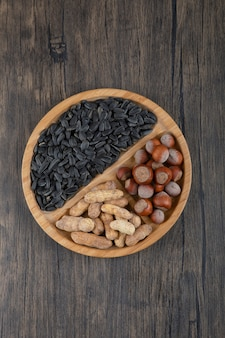 Houten bord vol gezonde noten en zwarte zonnebloempitten.