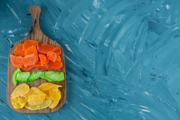 Houten bord vol met gedroogde vruchten op blauwe achtergrond.