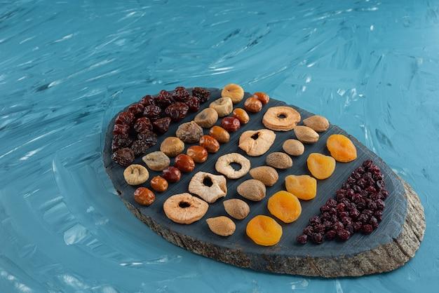 Houten bord vol met lekker gedroogd fruit op blauwe ondergrond.