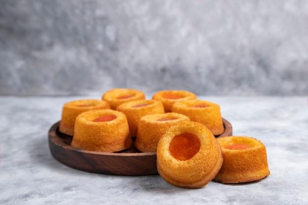 Houten bord vol zelfgemaakte abrikozenjam thumbprint cookies.
