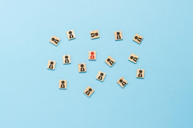 Houten borden met iconen van mensen met stropdassen verspreid op een blauwe achtergrond. corporate concept, creatief denken, leiderschap. plat lag, bovenaanzicht.
