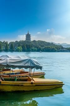 Houten boten en leifeng pagoda aangemeerd in hangzhou west lake