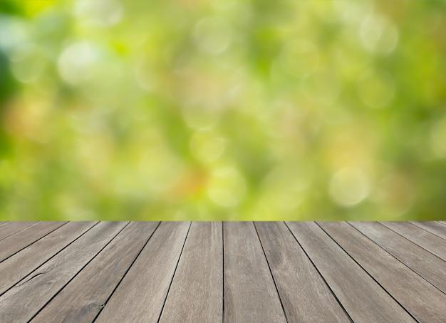 Houten bovenste tafel en groene wazig bokeh achtergrond