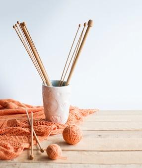 Houten breinaalden, plukjes draad, oranje plaid en met de hand gemaakt glas op een lichte houten achtergrond.