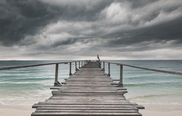 Houten brug en de zee met donkere regen bewolkt weinig licht.