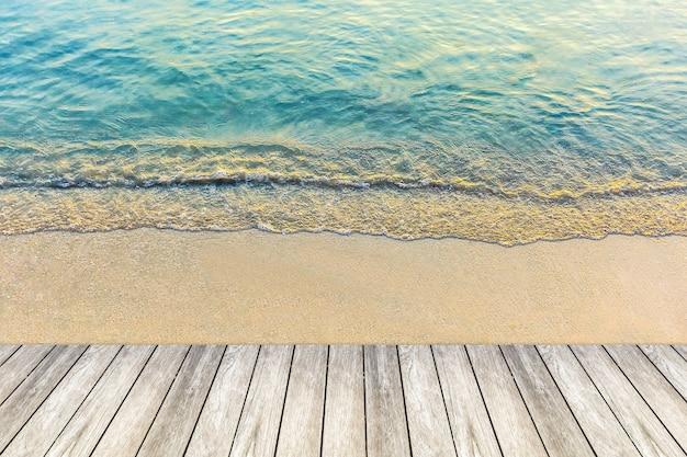 Houten brug en golf van het overzees op zandstrand