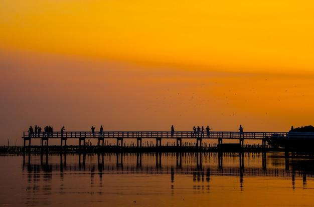 Houten brug en mensen tegen de achtergrond van de zonsonderganghemel