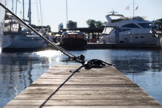 Houten brug in de haven waar het moderne en luxejachten dokken