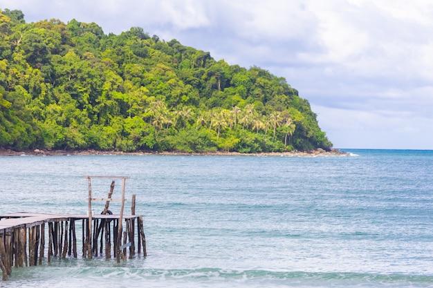 Houten brug in de zee met de lucht en het eiland als achtergrond