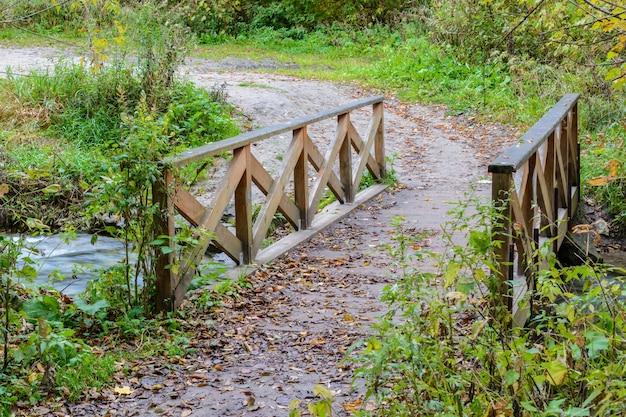 Houten brug in het bos bedekt met herfstgebladerte. herfst landschap in de buurt van het blauwe meer. kazan, rusland.