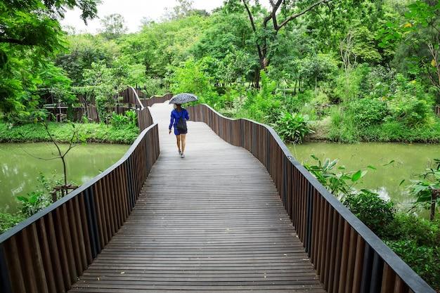 Houten brug met een vrouw die in een park loopt.