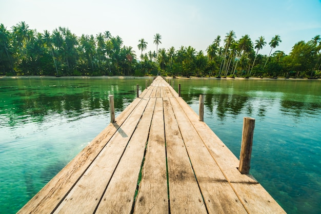 Houten brug of pier op het strand en de zee