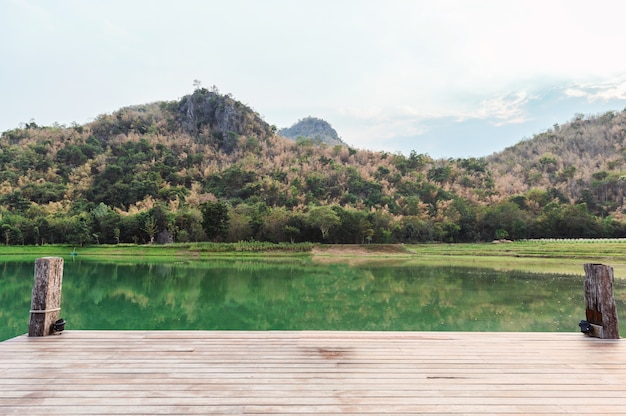 Houten brug of steiger met berg op meer
