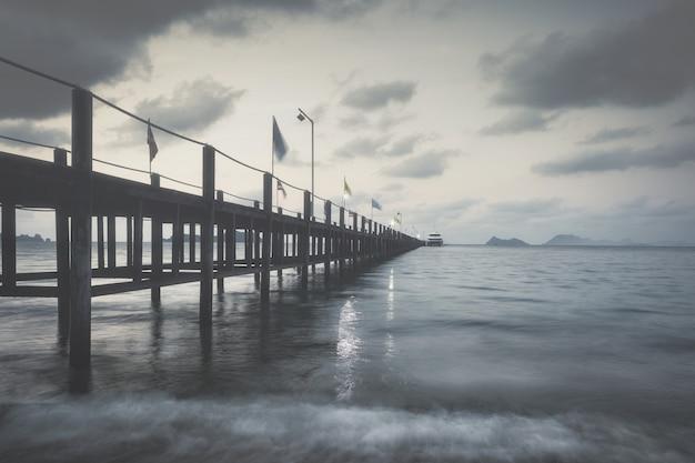Houten brug over de zee op een regenachtige dag