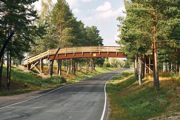 Houten brug over een asfaltweg op een zonnige zomerdag