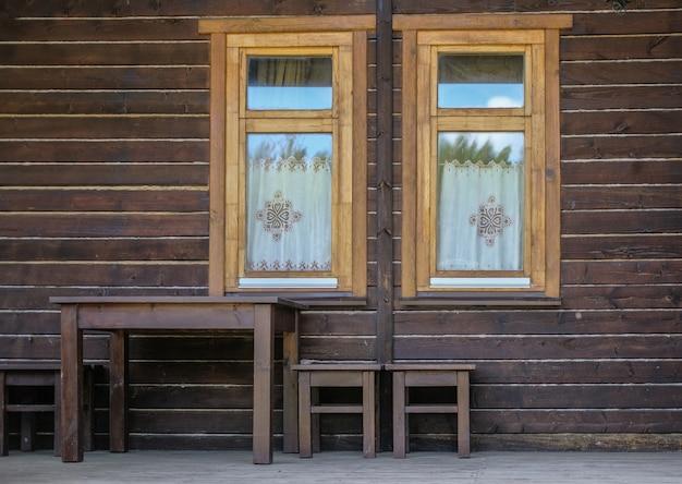 Houten bruine gevel van een vintage huis met twee ramen. houten tafel en krukken tegen de muur