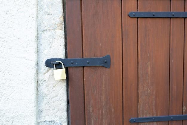 Houten bruine staldeur met hangend metalen slot buiten. ruimte kopiëren