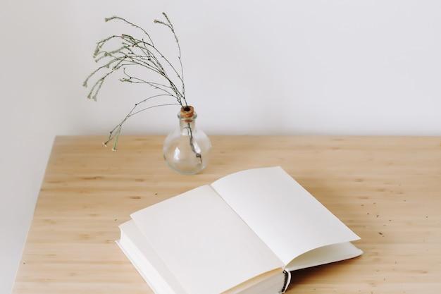 Houten bureau met boek en bloemen bovenaanzicht