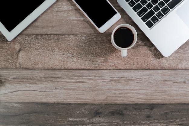 Houten bureau met computer, tablet en slimme telefoon met koffiekopje