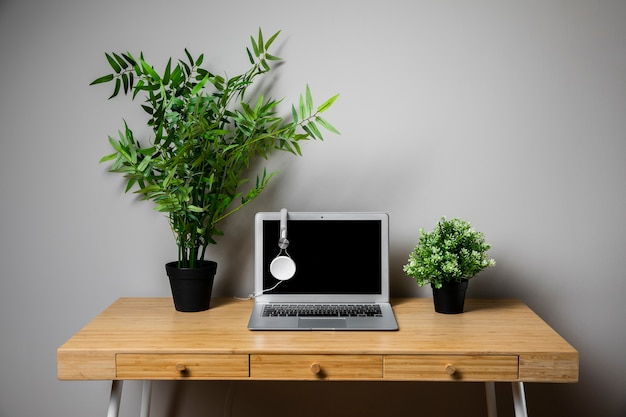 Houten bureau met grijze laptop en hoofdtelefoons