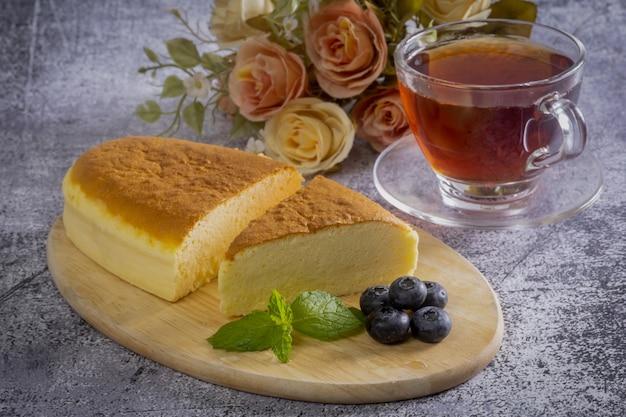 Houten bureau met japanse cheesecake en afternoon tea, close-up.
