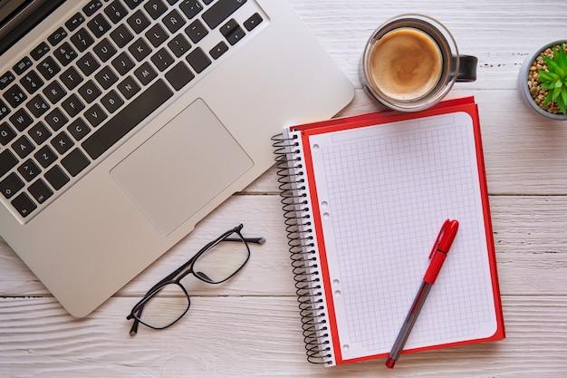 Houten bureau met laptop, notebook en koffie. concept van studie, werk en zaken.