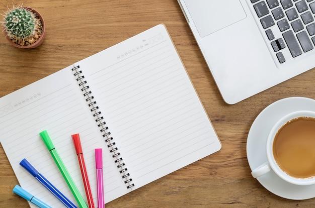 Houten bureau tafel met laptop, computer laptop, kleur pennen, cactus en kopje koffie. bovenaanzicht met kopie ruimte.