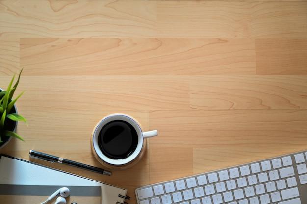 Houten bureaudesktop met toetsenbordcomputer, koffiemok, bureaulevering en exemplaarruimte