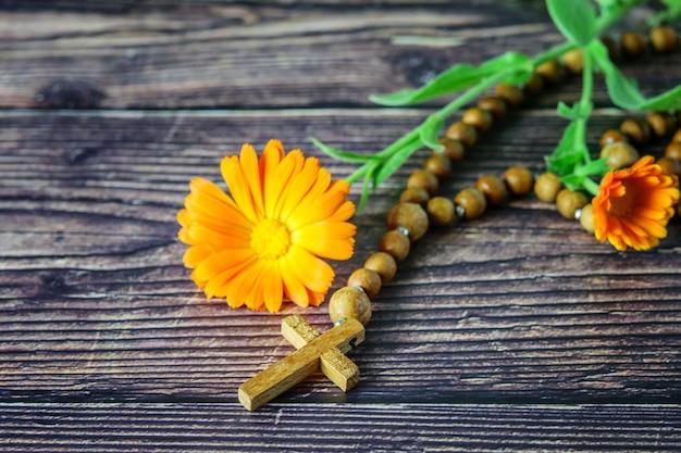 Houten christelijk kruis met chaplet en een bloem op donker hout