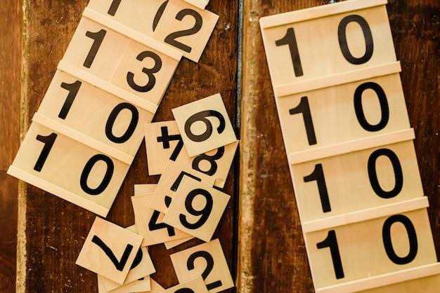 Houten cijfers in tabellen om wiskunde te leren in een montessoriklaslokaal.