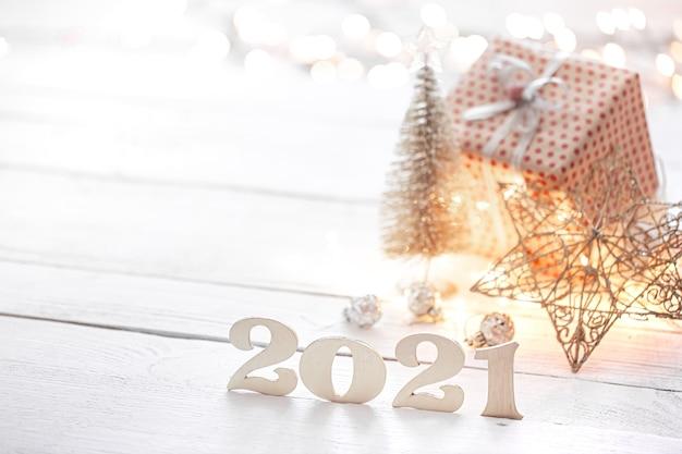 Houten cijfers op een onscherpe achtergrond van kerstversiering.