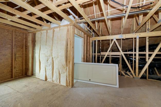 Houten dakbalken met isolatie van de zolder met buisverwarmingssysteem en minerale wol