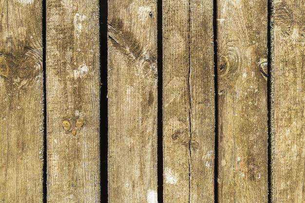 Houten de textuurachtergrond van de schuurraad met mos, verticale planken. oude houten achtergrond, donker bruin groen houten textuur natuurlijk buiten verouderd.