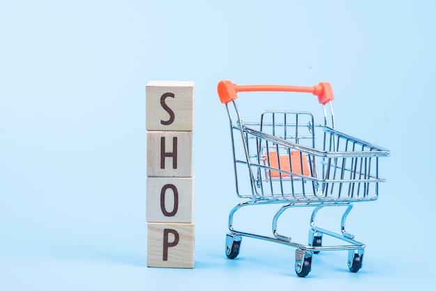 Houten de winkelwoord van het kubusblok met miniboodschappenwagentje op blauw